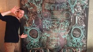 Cyrus Smith standing beside his work, displayed at the Deer & Almond restaurant in Winnipeg. Photo credit: Amber McGuckin.